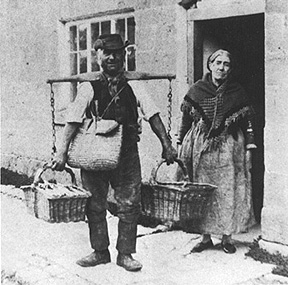 A tradesman delivering goods with a yoke near Broadway, Worcestershire, at the turn of the century (around 1900)