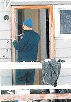 An unidentified officer uses a knife to retrieve pellets fired by RCMP Const. --Dave Voller. -Carlos Amat, SUN