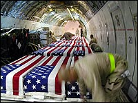 The flag-draped coffins of 21 soldiers killed in Iraq are carefully strapped down and checked before being returned to the United States aboard a military transport plane. Making that photograph cost the photographer her job.